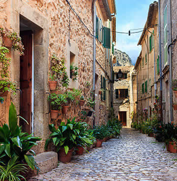 Valldemossa's cobbled streets lined with terracotta plant pots overflowing with greenery