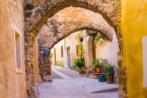 A series of archways over a quiet, cobblestone street in Les Adrets de l'Esterel