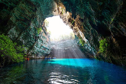 Light rays hit the electric blue waters of Melissani Lake