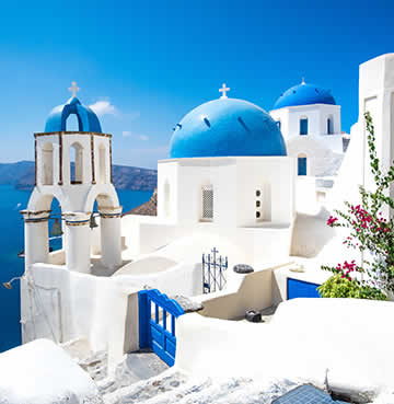 Blue-dome churches and whitewashed houses sit against a backdrop of the deep blue Santorini Caldera