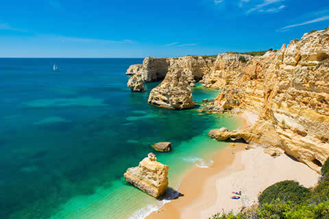 Golden cliffs and beach and turquoise sea waters of the Algarve