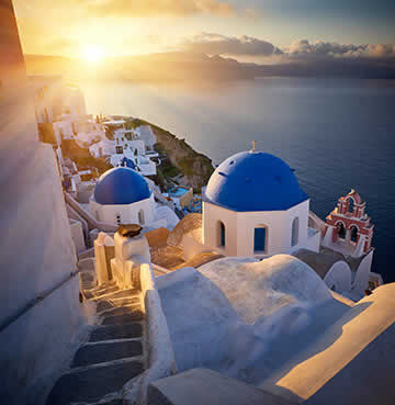 The sun sets over the iconic village of Oia and Santorini's caldera