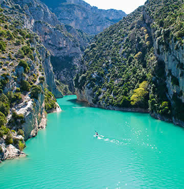 Aquamarine waters weave between the rising rock face of Verdon Gorge