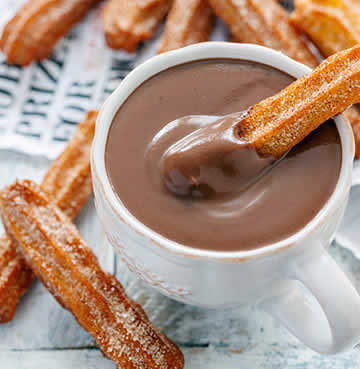 Churros and a cup of rich, melted dipping chocolate