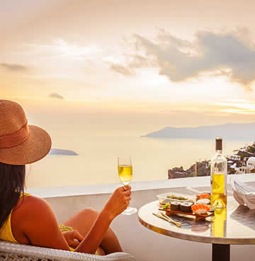 A woman enjoys a glass of crisp white wine in Santorini, Greece looking on at the sunset in Oia.