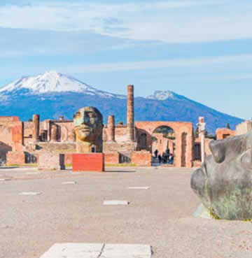 Fallen statues and ruins of Pompeii in Italy, with snow-topped mountains behind