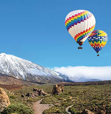 Hot air balloons flying above the mountains of Teide National Park in Tenerife