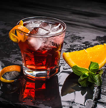 A Negroni and lemon are placed on a dark wooden table
