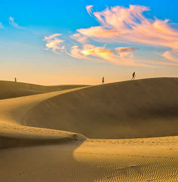 People walking across Maspalomas' iconic sand dunes as the sun sets