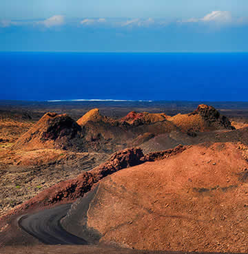 Timanfaya National Park's fire mountains, looking out towards the sea