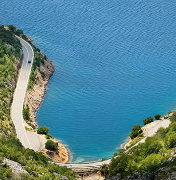 Winding coastal road, backed by lush vegetation