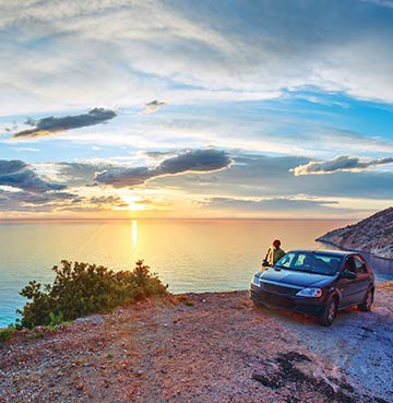 A traveller admiring the sunset and ocean views, standing next to their hire car.