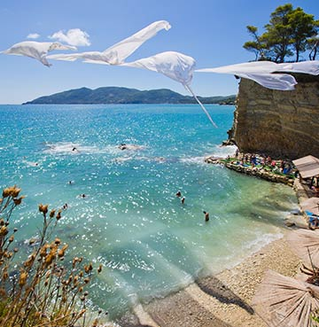 Beach decorations blowing in the gentle wind. Views across Cameo Island, Zakynthos