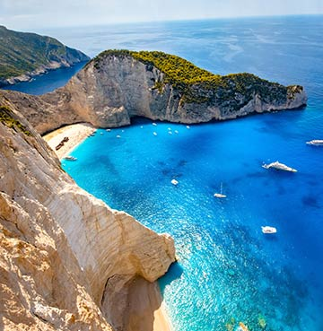 Turquoise sea and limestone craggy cliffs at Navagio Beach, Zakynthos