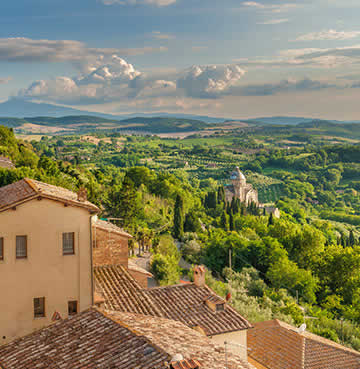 Luscious countryside and rolling hills, with a traditional Tuscan town in the foreground