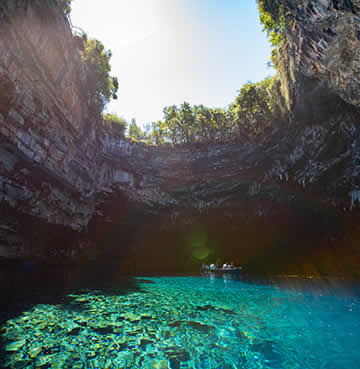 Glittering aquamarine waters at Melissani Cave as the sun pours through the cave's collapsed ceiling