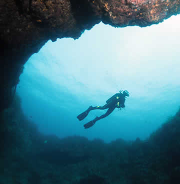 A scuba diver underwater, about to swim into a sea cave