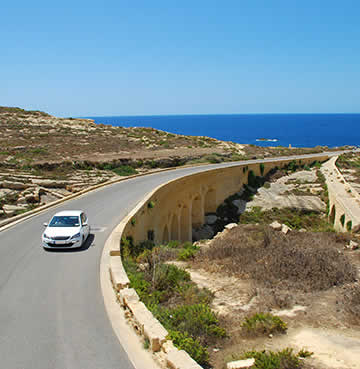 A white car driving along an elevated coastal road in Malta