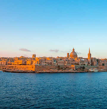 Valletta harbour at sunset, bathed in golden light.
