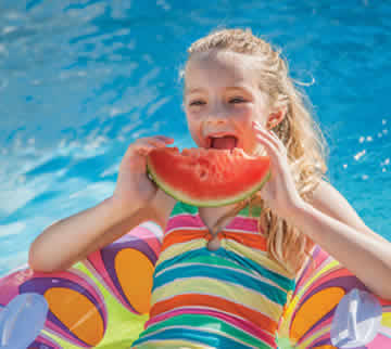 A girl eating a piece of watermelon in the pool