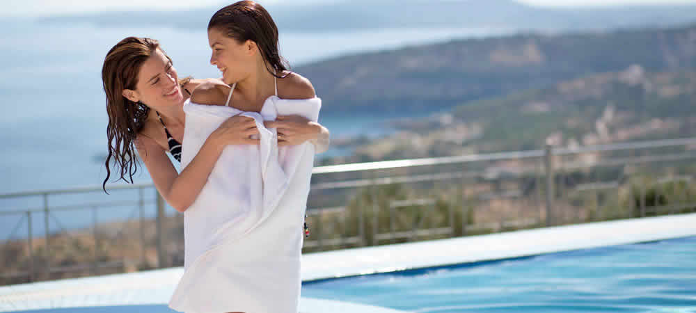 A mum cuddling her daughter in a towel by the pool