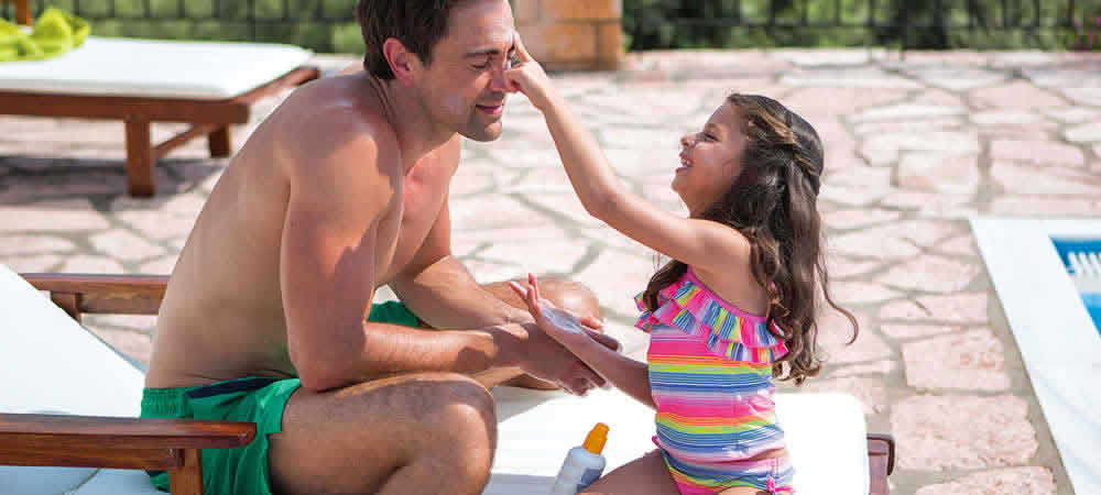 A girl putting sun cream on her dad's face