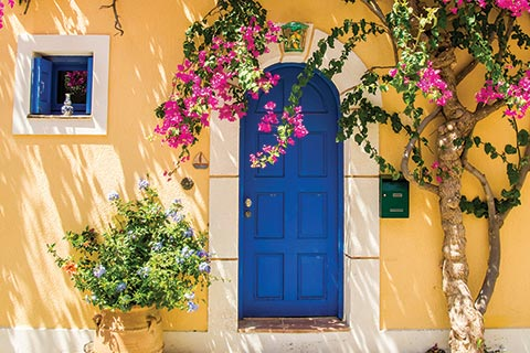 A bright blue door and yellow-painted house and surrounded by hot pink bougainvillea in Assos, Kefalonia