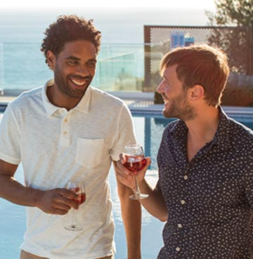 two men drinking wine together by the pool