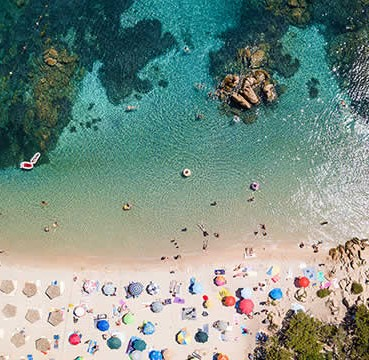 An aerial view of turqouise waters and powder-white sands of a beach in Ibiza. Umbrellas and parasoles are laid out neatly in a row.