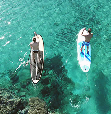 Two men stand up paddleboarding in azure Mediterranean waters in Ibiza