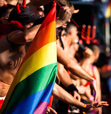 A rainbow flag being help proudly at Ibiza Gay Pride