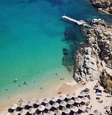 Azure waters lap at the golden sands of Paradise Beach, Mykonos. Rugged rocks and parasoles accessorize the shores.