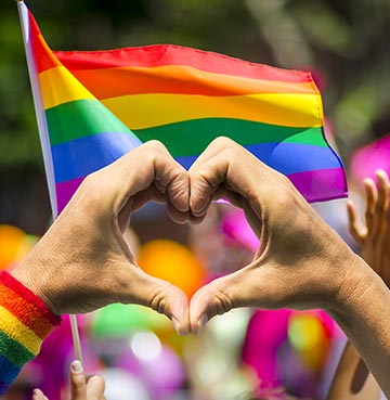 Hands forming a heart shape in front of a flag at an LGBT Pride event