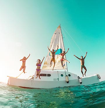 Five young people jumping from a yacht into turquoise ocean waters