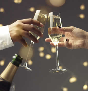 A couple toasting with a bottle of Cava at New Years celebrations