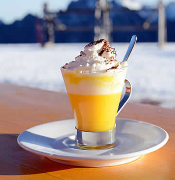Traditional Italian Bombardino on a wooden table with a snowy backdrop at a ski resort