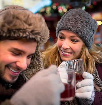 Young couple enjoying a glass of Vin Chaud at a Christmas market in France