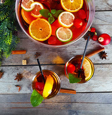 Aerial view of festive Sangria bursting with fruit laid out on a wooden table