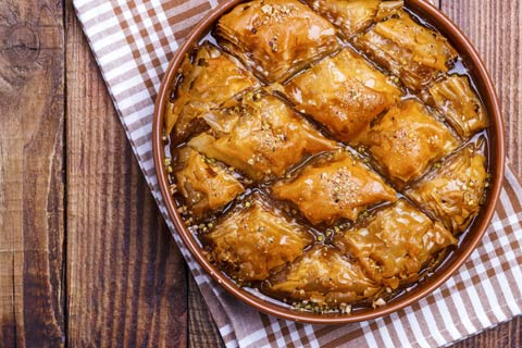 A bird's eye view of a rustic table with a freshly baked batch of Baklava