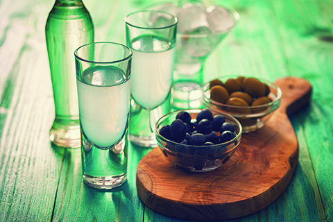 A glass bottle of Ouzo is laid out in a rustic table next to two glasses and a wooden cheese board