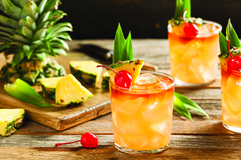 Three glasses of rum cocktails are laid out on a table with a prepared pineapple in the background