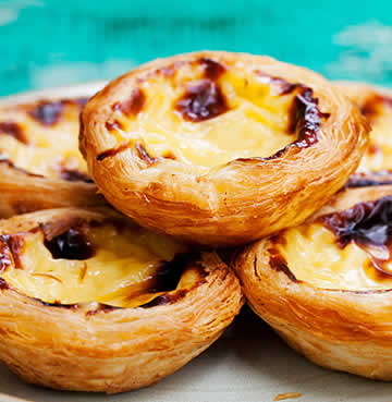 Pasteis de Nata stacked on a plate