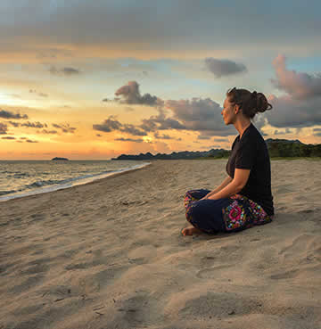 A woman meditates on a beach at sunrise