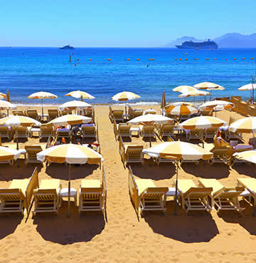 Golden, sandy beach covered in luxury sunloungers and parasols