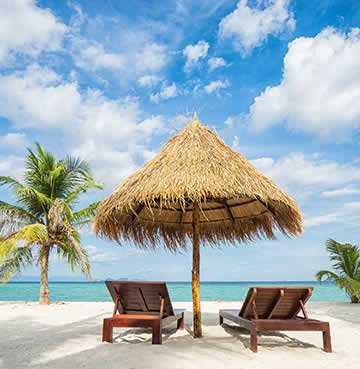 A straw parasol shelters two wooden sunloungers on a sandy beach in the Caribbean