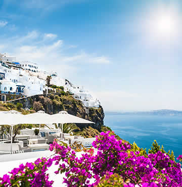 Whitewashed buildings perch on a rugged coastline with the Santorini caldera in the background