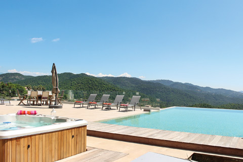 A contemporary infinity pool with wooden decking, overlooking the mountains in Cote d'Azur