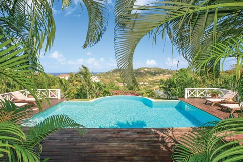 A unique shaped infinity pool with traditional white fencing and wooden decking is surrounded by luscious vegetation in St. Lucia
