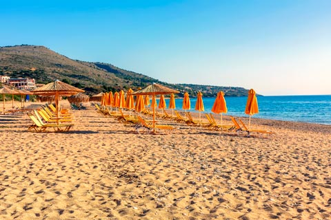 The golden, sandy beach at Skala is lined with orange sunloungers and parasols