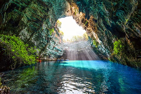 Sunlight pours through the collapsed roof at the infamous Melissani Lake